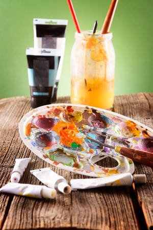 putty: Professional acrylics paints in tubes, palette with artistic putty knife and brushes in a jar with water