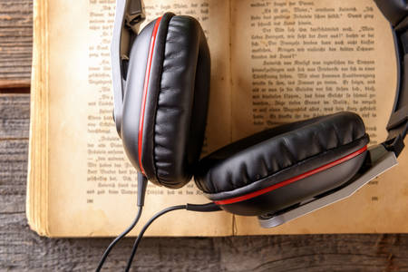 music book: Headphones on the old book. Concept of listening to audiobooks.