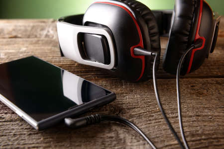 portable mp3 player: Headphones with mobile phone on wooden desk