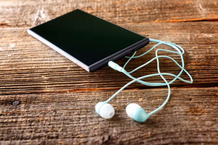 portable mp3 player: Small headphones with mobile phone on wooden desk Stock Photo