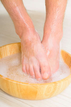 feet washing: Male feet in a bowl with water and soap, hygiene and spa concept Stock Photo