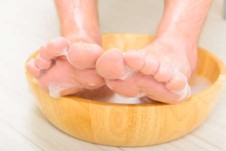 soaking: Male feet in a bowl with water and soap, hygiene and spa concept Stock Photo