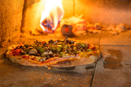 Fresh original Italian pizza in a traditional wood-fired stone oven.