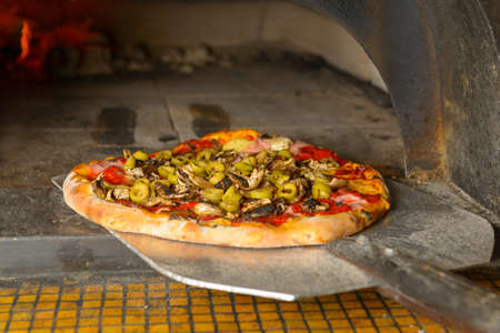 woodfired: Fresh original Italian pizza on a shovel is putting into a traditional wood-fired stone oven.