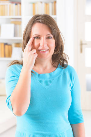 Woman doing EFT on the side of eye point. Emotional Freedom Techniques, tapping, a form of counseling intervention that draws on various theories of alternative medicine. photo
