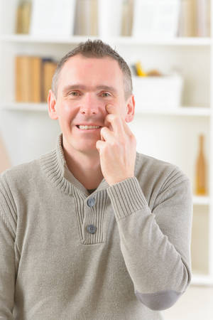 Man doing EFT on the under eye point. Emotional Freedom Techniques, tapping, a form of counseling intervention that draws on various theories of alternative medicine. photo