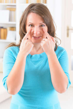 Woman doing EFT on the under eye point. Emotional Freedom Techniques, tapping, a form of counseling intervention that draws on various theories of alternative medicine.