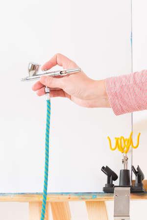 airbrushing: Mano que sostiene un aer�grafo profesional sobre lienzo blanco o fondo Foto de archivo
