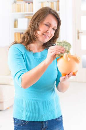 piggybank: Woman putting money in piggybank, concept of saving