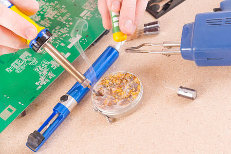 impedance: Serviceman soldering PCB with soldering iron in the service workshop