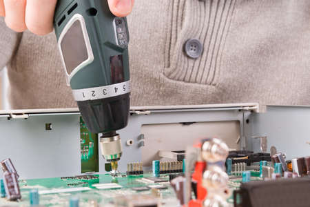 impedance: Unscrewing bolt with a cordless screwdriver on PCB Stock Photo