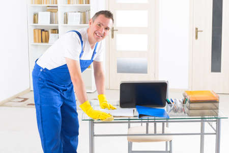 self service: Smiling man cleaner wiping table at the office