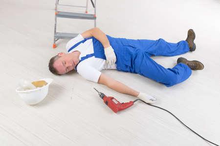 para baixo: O trabalhador do homem coloca em um assoalho, conceito de acidente de trabalho