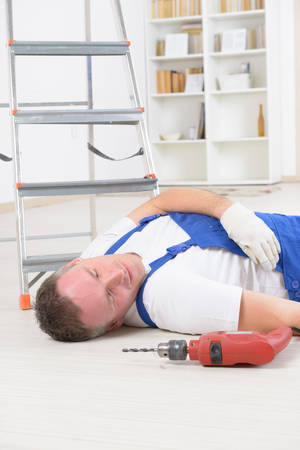 personal injury: Man worker laying on a floor, concept of accident at work