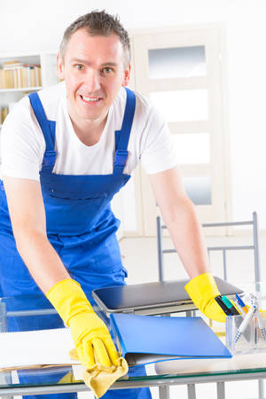 clean office: Smiling man cleaner wearing yellow gloves and cleaning office table
