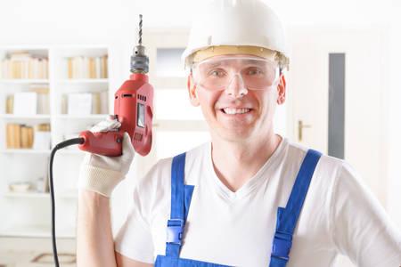 taladro: Hombre sonriente con el taladro eléctrico llevaba casco protector y gafas