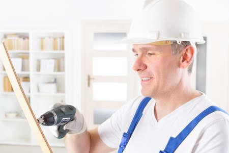 herramientas de construccion: Hombre sonriente con el pequeño taladro inalámbrico llevaba casco protector y gafas Foto de archivo