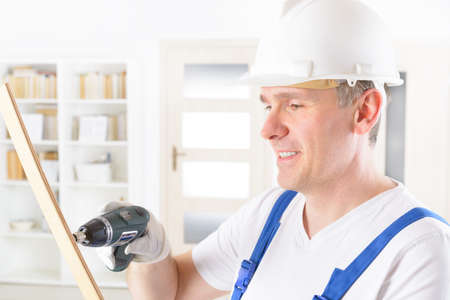 electric tools: Smiling man with small wireless drill wearing protective helmet and glasses