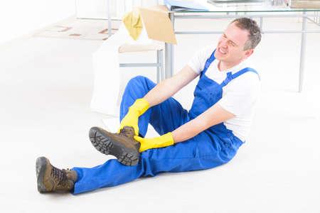 Muž pracovník s zranění kotníku, pojem úrazu při práci Reklamní fotografie