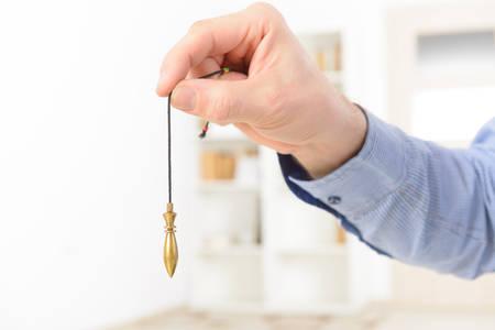 Hand with pendulum, tool for dowsing.