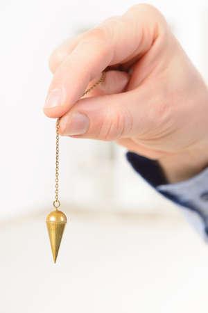 Hand mit Pendel, Werkzeug für die Wünschelrute.