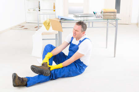 Man worker with ankle injury, concept of accident at work