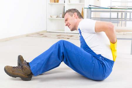Man werknemer met rugletsel, concept van een ongeval op het werk Stockfoto