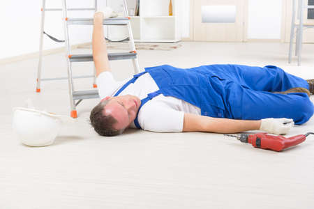 work safety: Man worker laying on a floor, concept of accident at work