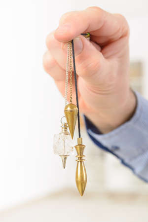 dowsing: Hand with many pendulums crystal pendulum, copper, karnak, tool for dowsing.