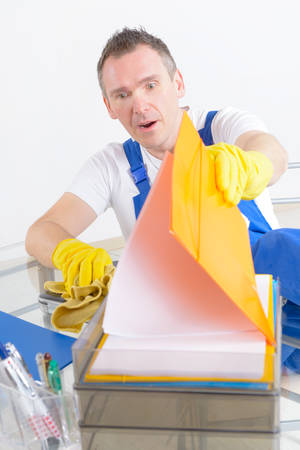 dishonest: Dishonest or curious man cleaner looking at the papers Stock Photo
