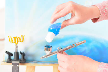 airbrushing: Adding blue paint to a professional airbrush