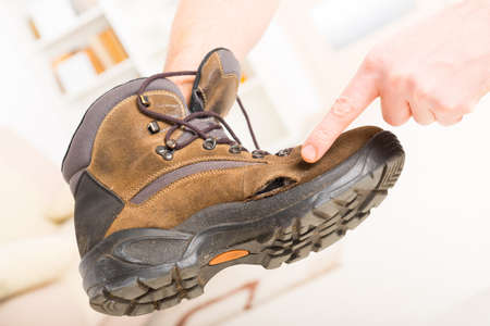 holed: Hole in worn old shoe