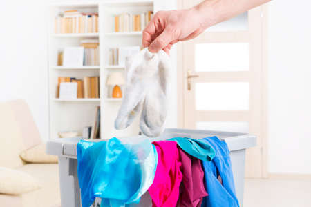 muddy clothes: Hand holding dirty white socks over a hamper or basket