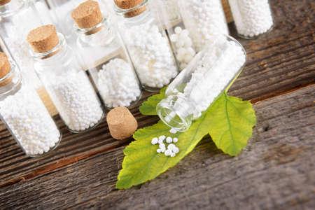 globules: Homeopathic lactose sugar globules on leaf with glass bottle Stock Photo
