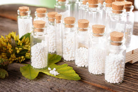globules: Homeopathic lactose sugar globules in glass bottles with plants Stock Photo
