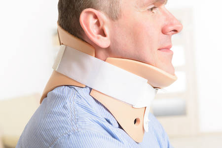 accident patient: Man with a surgical cervical collar suffering from neck pain