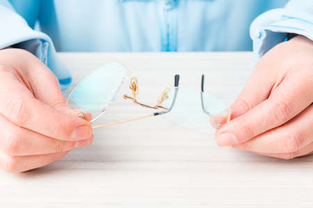 vision repair: Hands holding old, broken glasses