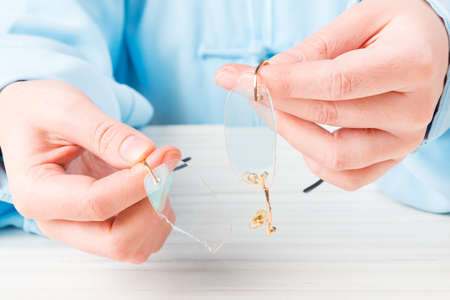 vision repair: Hands holding old, broken glasses