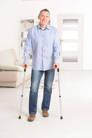 disabled person: Man walking with crutches, rehabilitation after injury