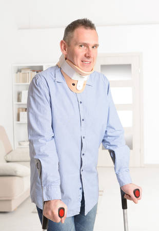 recovering: Standing man with crutches and cervical collar Stock Photo