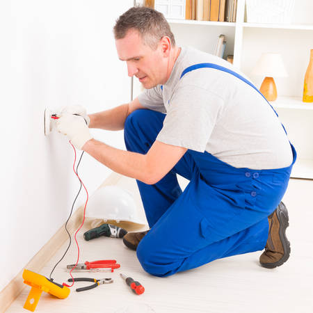 installation: Electrician checking socket voltage with digital multimeter
