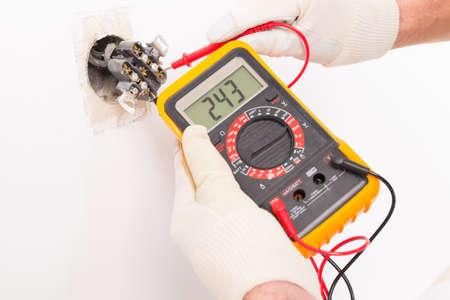 mantenimiento: Electricista tensi�n toma de cheques con mult�metro digital Foto de archivo