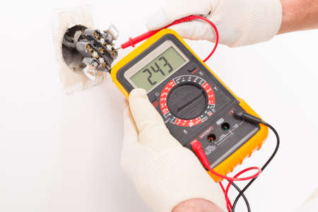 Elektricien controle socket spanning met digitale multimeter Stockfoto