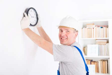 timekeeping: Smiling man hanging wall clock wearing protective helmet
