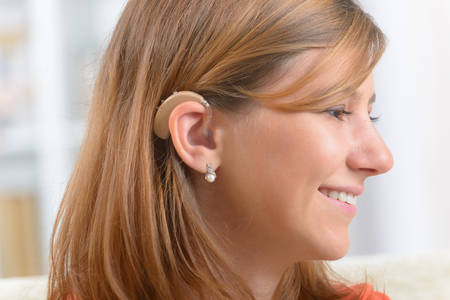 Young, smiling woman wearing deaf aid Stock Photo