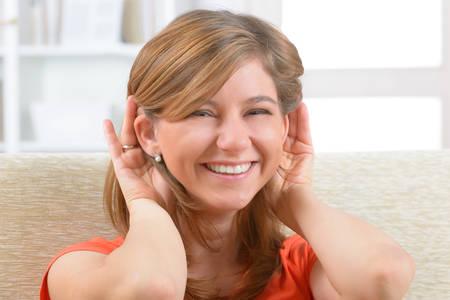 persona enferma: Mujer joven, sonriente llevaba ayuda sordos