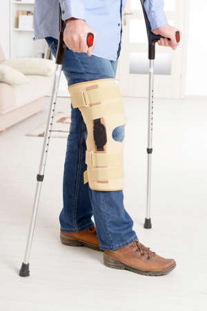 braces: Man with leg in knee cages and crutches for stabilization and support Stock Photo