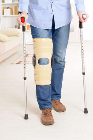 therapeutical: Man with leg in knee cages and crutches for stabilization and support Stock Photo