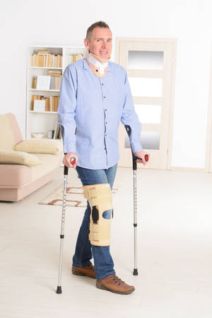 neck brace: Man with leg in neck brace, knee cages and crutches for stabilization and support