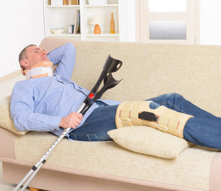 neck brace: Man with leg in neck brace, knee cages and crutches for stabilization and support resting on a sofa